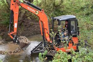 Spreading gravel in the brook